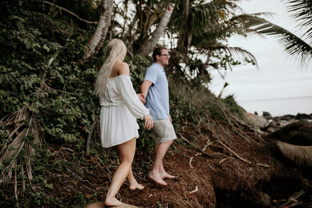 couple holding hands hiking barefoot on little corn island